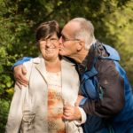 Older couple walking in a park man is kissing her on the cheek and she is smiling