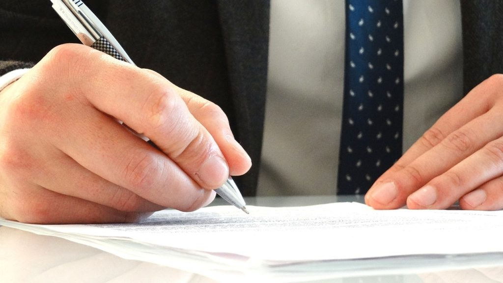 Close up of man's hands signing a contract