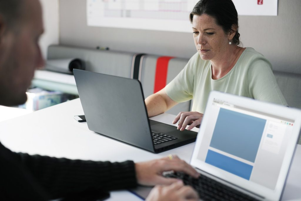 Man and woman working on laptops at a shared desk