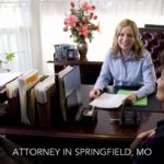Sativa Boatman-Sloan sitting at her desk talking with a man and woman