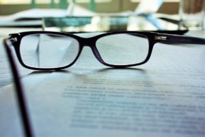 Glasses sitting on top of a stack of papers with text on them