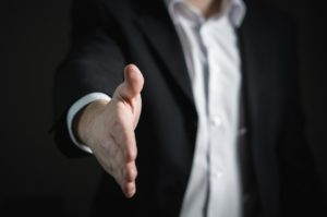 Man in a business suit holding his hand toward the camera like he wants to shake hands