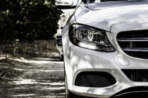 Close up of the headlight of a white sporty vehicle parked on a road