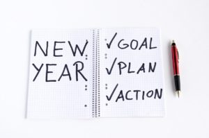 """Notebook with grid paper with the words """"New Year' written on one side and """"Goal, Plan, Action"""" with checkmarks on the other side with pen lying next to it"""