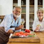 Older couple in kitchen holding wine glasses