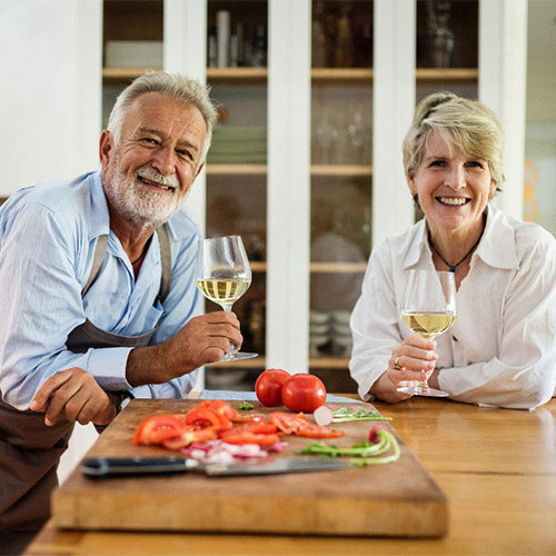 older couple in kitchen holding wine glasses and smiling