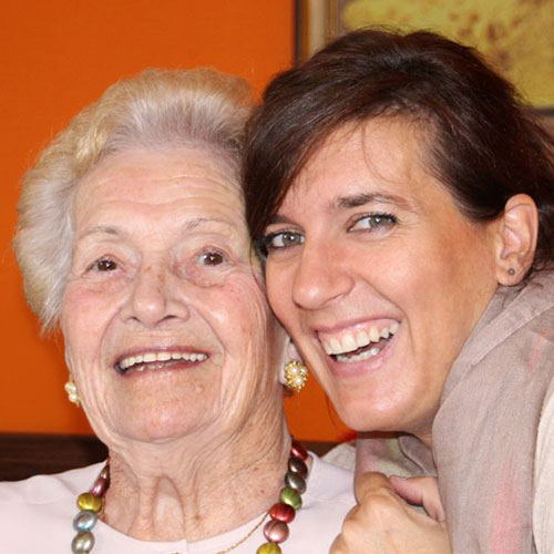 older woman and younger woman looking at the camera and smiling