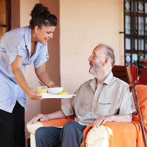 womand handing a full food tray to older man in chair